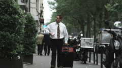 Businessman walking down a city street in Europe dragging a suitcase and looking Stock Footage