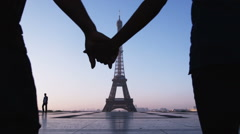 Couple kissing and holding hands in front of the Eiffel tower Stock Footage