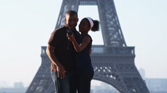 Couple taking their own photo in front of the Eiffel tower Stock Footage