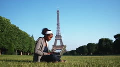 Woman sitting on the grass in front of the Eiffel tower working on a laptop Arkistovideo