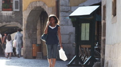 Woman walking down a European street talking on a cell phone Stock Footage