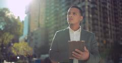 Young African American black Latino man in city using tablet pc 4k Stock Footage
