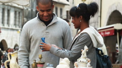 Young couple shopping for glassware in a European outdoor market Stock Footage