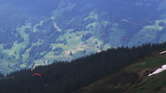 Paragliders soaring above an alpine valley Stock Footage