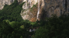 Castle at the base of a mountain waterfall Stock Footage