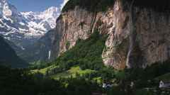 Village at the base of a mountain waterfall Stock Footage