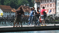 Couple taking a photo of themselves on a bridge when a passerby stops to take it Stock Footage