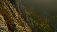 AERIAL: Big vertical rock wall above mountain valley Stock Footage