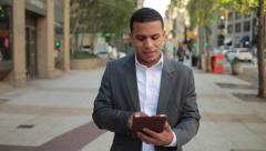 Young African American black Latino man in city walking using tablet pc - stock footage