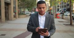 Young African American black Latino man in city walking using tablet pc 4k Stock Footage