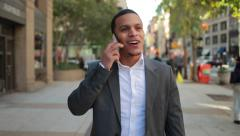 Young African American black Latino man in city walking talking on cellphone Stock Footage