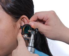 ent physician checking patient's ear using otoscope with an instrument - stock photo