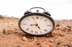 classic analog clock in the sand - stock photo