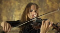 Lovely girl in black dress playing the violin on a vintage background Arkistovideo