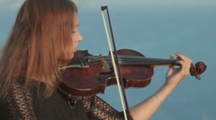 Young violinist in tracery dress plays on a rock by the sea Stock Footage