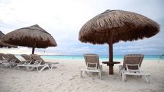 Sun umbrellas and chaise-longue on caribbean beach Stock Footage