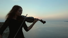 Beautiful violinist playing while the sun is almost gone over the horizon at sea Stock Footage