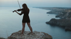 Young girl in short dress standing on a cliff, playing the violin and looking at Stock Footage