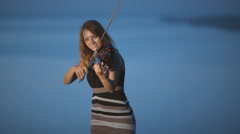 Creative girl playing the violin standing on a cliff next to blue sea Stock Footage