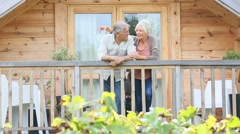 Senior couple standing oustide log cabin in countryside Stock Footage