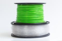 Filament for 3d printer crystal clear and bright green against a bright backg Stock Photos