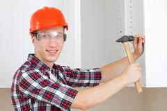 Repairman in a helmet with a hammer Stock Photos
