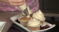 A woman is preparing cupcakes with delicious cream Stock Footage