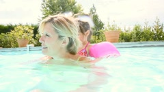 Mother and daughter swimming in private pool Stock Footage