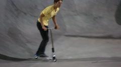 Teen rides razor at skate park at night Stock Footage