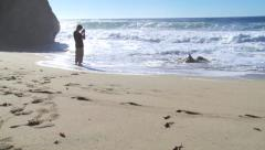 Man stands in surf taking pictures Stock Footage