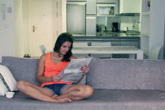 Woman sitting cross-legged and reading newspaper on the sofa - stock footage