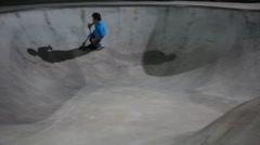 Teens rides razors at skate park at night Stock Footage