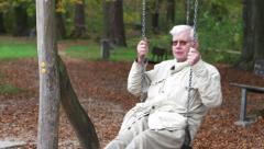 Senior man enjoying a swing. - stock footage
