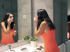 Woman putting moisturizing cream under her eyes in the bathroom Stock Footage