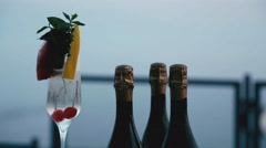 Cocktail with bubbles, champagne bottles and sea background Stock Footage