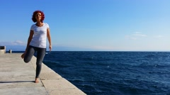 Woman performing joga on sea coast, on windy sunny day Stock Footage