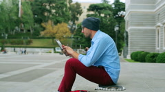 Man working on tablet and sitting on public square Stock Footage