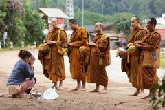 Buddhist monks alms in thailand Stock Photos