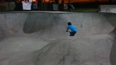 Teens practice tricks at skate park at night Stock Footage