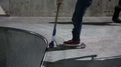 Teens riding razors at skate park at night Stock Footage