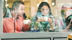 People drinking coffee and using cellphone behind cafe window - stock footage
