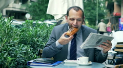 Businessman having a break in the street cafe and reading gazette Stock Footage