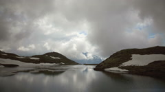 Time lapse of clouds passing over a mountain lake Stock Footage