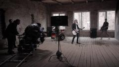 The cameraman on a trolley Dolly shoots music video with rock band Stock Footage