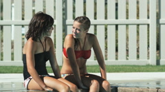 two girls by the pool splashing a boy - stock footage