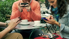 People using smartphone in the street cafe, steadycam shot Stock Footage