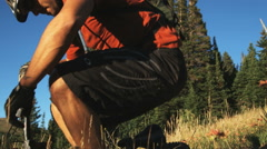 Mountain biker sitting down to rest Stock Footage