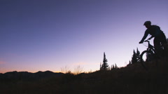 Mountain bikers riding at sunset Stock Footage