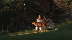 Woman and little girl petting a fawn Stock Footage