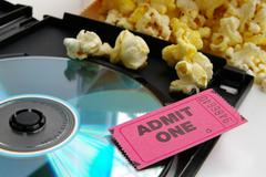 ticket stub and popcorn with dvd closeup - stock photo